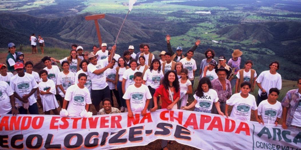 """Foto mostra grupo de pessoas segurando uma faixa onde se lê """"Quando estiver na Chapada, Ecologize-se"""", com a parte baixa da paisagem da chapada ao fundo"""