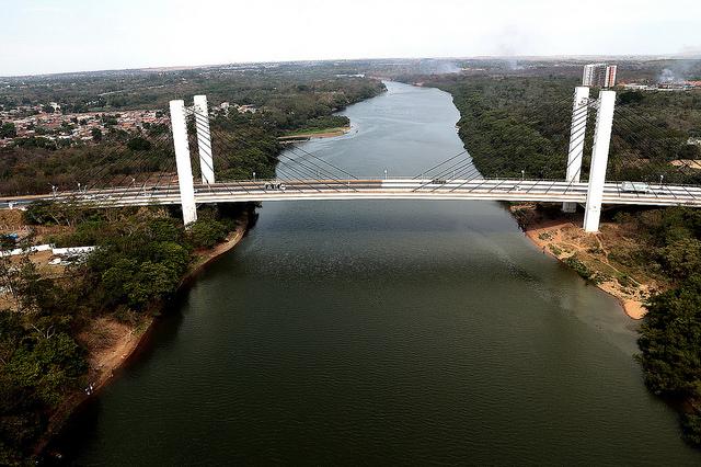 Foto mostra uma ponte atravessando o rio cuiabá no centro, e nas bordas a vegetação da beira do rio e áreas com edifícios