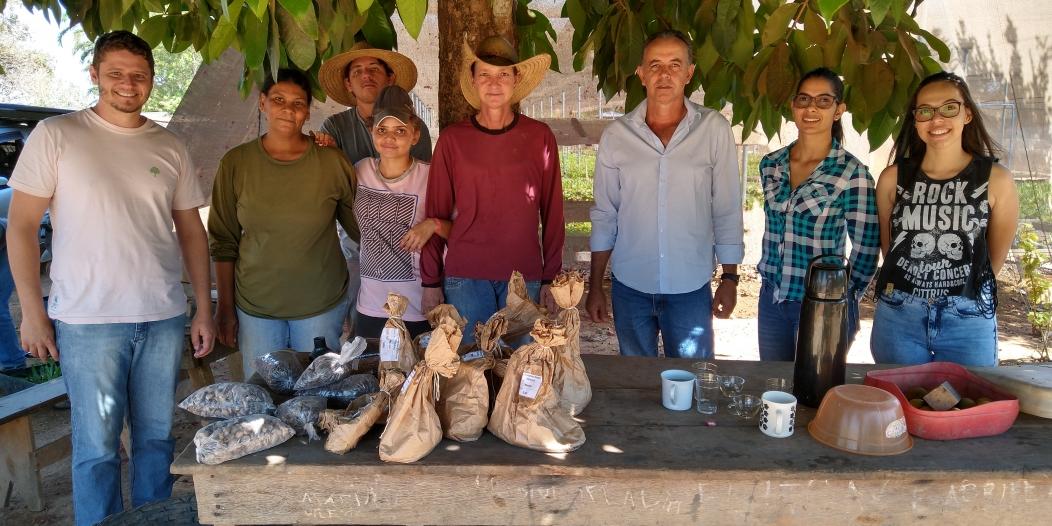 A foto mostra um grupo de 8 pessoas, homens e mulheres , em um local aberto com mudas cultivadas ao fundo. As pessoas estão atrás de uma mesa sobre a qual estão alguns sacos de sementes.