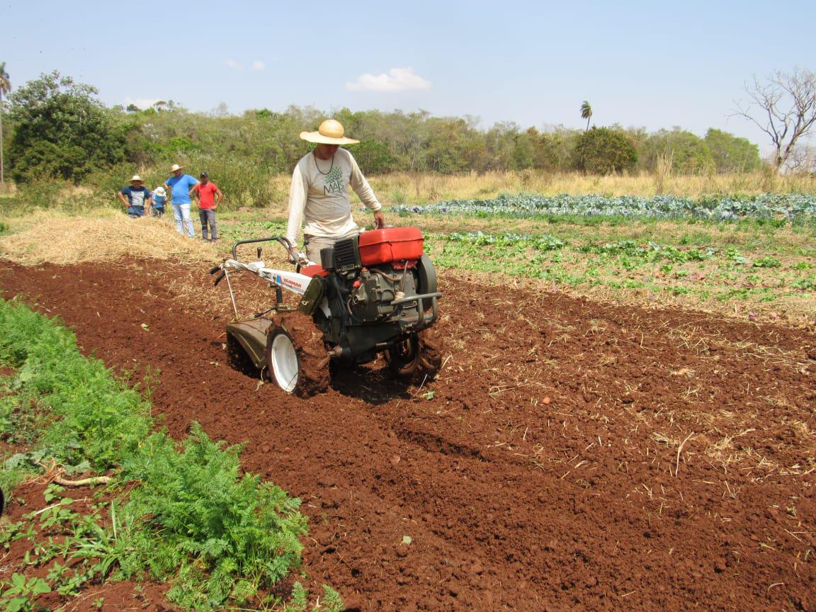 Foto mostra grupo agricultor manejando máquina sementeira e plantando sementes em uma área de cultivo de agrofloresta