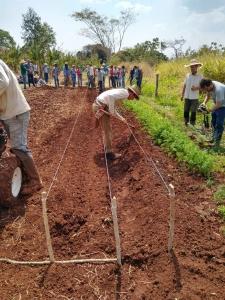 Foto mostra agricultor com enxada trabalhand a terra em trechos demostrativo de agrofloresta demarcado com galhos e linhas de cordão e demais pessoas em volta observando