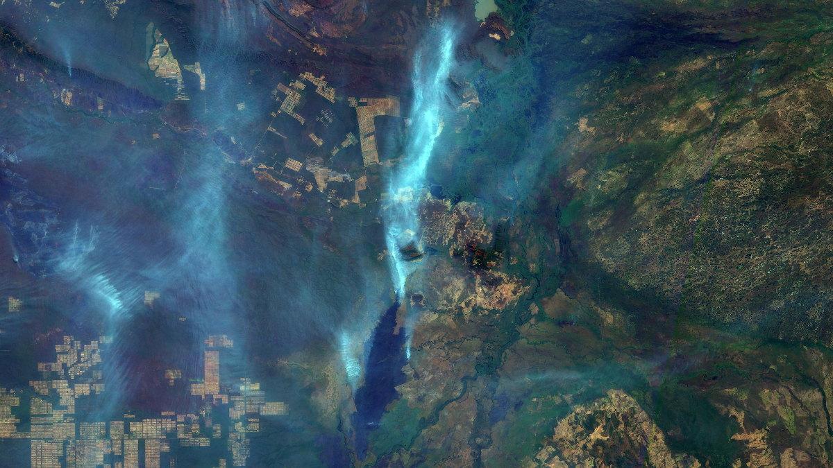 Cicatriz de queimada no Pantanal com +1000 km2, a 60 km a SSO de Corumbá, em preto. Ainda com queimadas ativas, evidenciadas por suas plumas de fumaça em branco